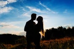 Schattenbild eines jungen Paarumarmens lizenzfreie stockfotos
