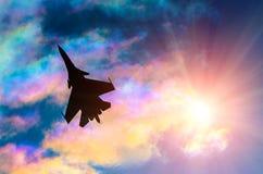 Schattenbild eines Kampfflugzeugs auf einem Hintergrund von schillernden Himmelwolken und -sonne Lizenzfreies Stockbild