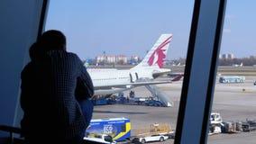 Schattenbild eines kleinen Jungen und des Vaters vor dem Terminalfenster, welches die Fl?chen betrachtet stock video footage