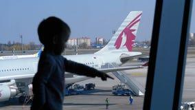 Schattenbild eines kleinen Jungen vor dem Terminalfenster, welches die Flächen betrachtet stock video footage