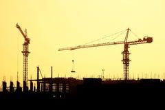 Schattenbild eines Kranes und des Rahmens eines Gebäudes im Bau stockbilder