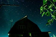 Schattenbild eines Landhauses vor dem hintergrund des sternenklaren nächtlichen Himmels und der Milchstraßegalaxie Lizenzfreies Stockbild