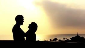Schattenbild eines liebevollen Paares, das nahe dem Meer auf dem Balkon bei Sonnenuntergang umarmt und küsst stock footage