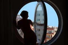 Schattenbild eines Mädchens auf dem Hintergrund des Fensters Stockfotografie