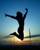 Schattenbild eines Mädchens, das über Sonnenuntergang springt Stockbilder