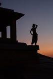 Schattenbild eines Mädchens, das den Sonnenuntergang betrachtet Lizenzfreie Stockfotos