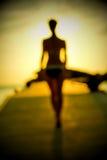 Schattenbild eines Mädchens, das entlang den Pier bei Sonnenuntergang geht Lizenzfreie Stockfotos