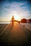 Schattenbild eines Mädchens, das entlang den Pier bei Sonnenuntergang geht Lizenzfreies Stockfoto