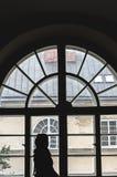 Schattenbild eines Mädchens vor einem alten großen Fenster Lizenzfreie Stockfotografie