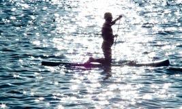 Schattenbild eines Mannes auf Radschaufel im Meer Lizenzfreies Stockfoto