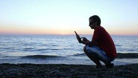Schattenbild eines Mannes bei dem Sonnenuntergang, der auf der Ufergegend mit einem Tablet-Computer sitzt Es überprüft die Mittei stock footage