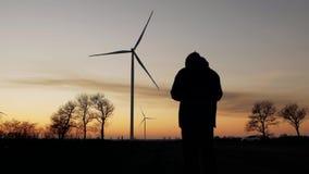 Schattenbild eines Mannes bei dem Sonnenuntergang, der ein Foto von den Windkraftanlagen macht stock video