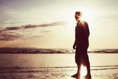 Schattenbild eines Mannes bei Sonnenaufgang auf dem Meer Lizenzfreie Stockfotos