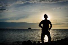 Schattenbild eines Mannes, der allein auf Küste mit schönem Himmel auf dem Hintergrund steht lizenzfreie stockbilder