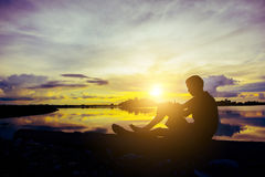 Schattenbild eines Mannes der, der auf Sonnenuntergang im Flussufer sitzt Lizenzfreie Stockfotos