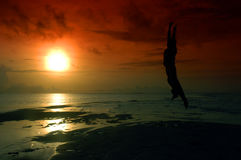 Schattenbild eines Mannes, der in den Sonnenaufgang springt Stockbild