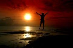 Schattenbild eines Mannes, der in den Sonnenaufgang springt Stockbilder