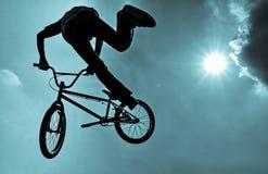 Schattenbild eines Mannes, der einen extremen Sprung BMX tut Lizenzfreie Stockbilder