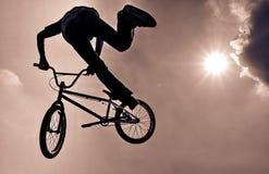 Schattenbild eines Mannes, der einen extremen Sprung BMX tut stockbild