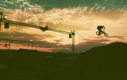 Schattenbild eines Mannes, der einen Sprung mit einem bmx Fahrrad tut Stockfoto