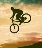 Schattenbild eines Mannes, der einen Sprung mit einem bmx Fahrrad tut Lizenzfreie Stockbilder