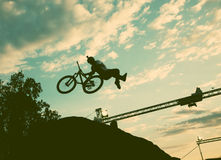Schattenbild eines Mannes, der einen Sprung mit einem bmx Fahrrad tut Stockfotos