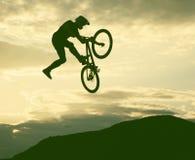 Schattenbild eines Mannes, der einen Sprung mit einem bmx Fahrrad tut Lizenzfreies Stockfoto