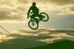 Schattenbild eines Mannes, der einen Sprung mit einem bmx Fahrrad tut Lizenzfreie Stockfotografie