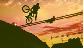 Schattenbild eines Mannes, der einen Sprung mit einem bmx Fahrrad tut Lizenzfreie Stockfotos