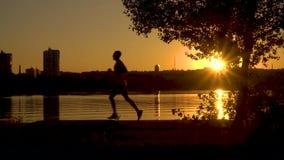 Schattenbild eines Mannes, der entlang die Promenade läuft stock video