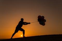 Schattenbild eines Mannes, der mit Ballonen bei Sonnenuntergang spielt Lizenzfreies Stockbild
