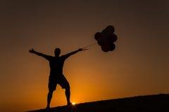 Schattenbild eines Mannes, der Spaß mit Ballonen bei Sonnenuntergang hat Lizenzfreie Stockfotos
