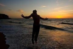 Schattenbild eines Mannes, der am Strand springt Stockbild