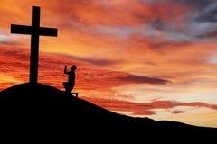 Schattenbild eines Mannes, der unter dem Kreuz betet Lizenzfreie Stockbilder