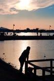 Schattenbild eines Mannes durch das Meer den Sonnenuntergang aufpassend Stockbild