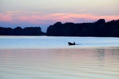 Schattenbild eines Mannes in einem Boot, das in den Fluss bei Sonnenuntergang schwimmt Stockbilder