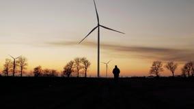 Schattenbild eines Mannes geht zum Sonnenuntergang in Richtung der Windkraftanlagen stock video