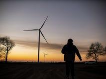 Schattenbild eines Mannes geht zum Sonnenuntergang in Richtung der Windkraftanlagen stockfoto