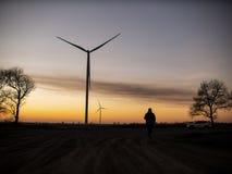 Schattenbild eines Mannes geht zum Sonnenuntergang in Richtung der Windkraftanlagen lizenzfreie stockfotos