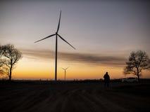 Schattenbild eines Mannes geht zum Sonnenuntergang in Richtung der Windkraftanlagen lizenzfreie stockfotografie