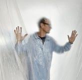 Schattenbild eines Mannes hinter Plastik Lizenzfreies Stockbild