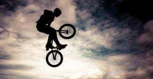 Schattenbild eines Mannes mit bmx Fahrrad. Stockbild