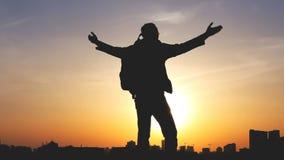 Schattenbild eines Mannes mit einem Rucksack gegen hellen Himmelsonnenuntergang stock footage