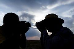 Schattenbild eines Mannes mit einer Kamera auf einem Sonnenunterganghintergrund Lizenzfreies Stockfoto
