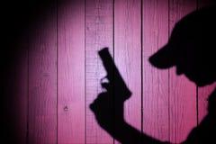 Schattenbild eines Mannes mit einer Pistole Stockfotografie