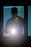 Schattenbild eines Mannes mit Taschenlampe Lizenzfreies Stockfoto