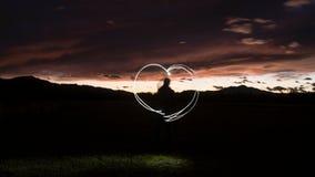Schattenbild eines Mannes zeichnet eine Herzform mit einem Taschenlampe throug Stockfoto