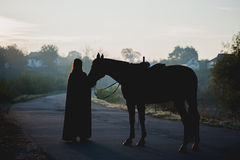 Schattenbild eines Mädchens in einem Regenmantel ein Pferd auf dunklem Hintergrund mit blauem Nebel küssend Lizenzfreie Stockfotografie