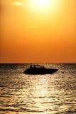 Schattenbild eines Motordrehzahlbootes bei Sonnenuntergang Lizenzfreie Stockbilder