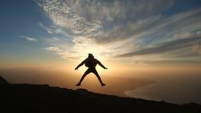 Schattenbild eines optimistischen Mannes, der gegen einen schönen Sonnenuntergang in der Zeitlupe springt stock video